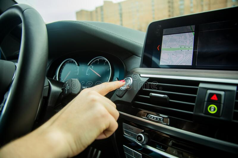 Female finger presses start stop engine button on a car dashboard. close-up, soft focus, in the background car interior. Female hand with finger presses the royalty free stock image