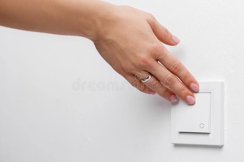 Finger turning off light switch. Female finger turning on or off light switch on wall royalty free stock photography