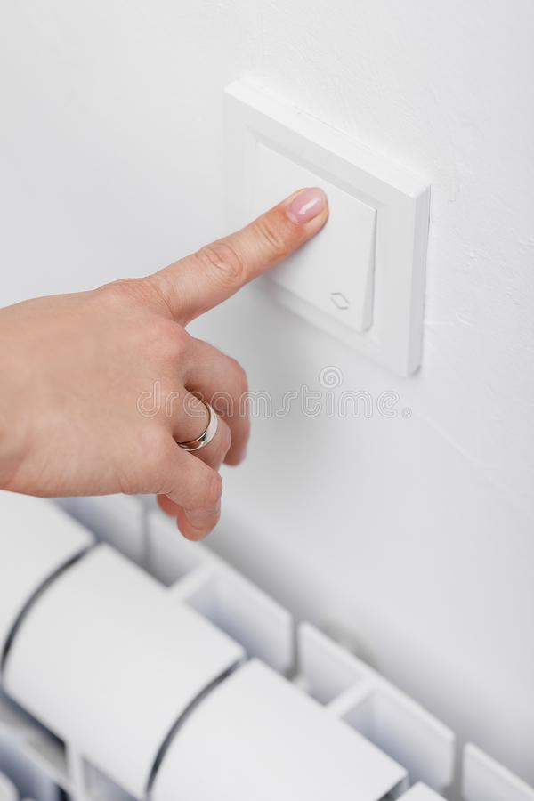 Finger turning off light switch. Female finger turning on or off light switch on wall royalty free stock images