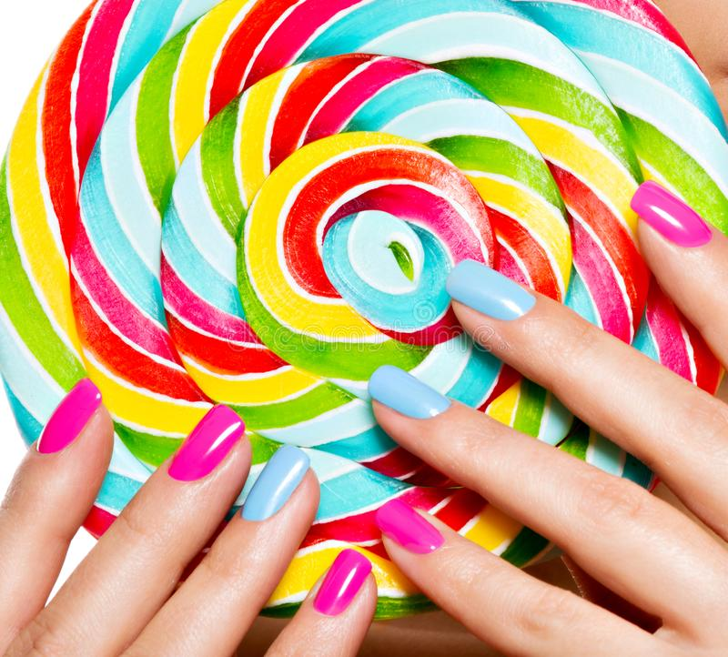 Female fingers with colorful nails on the background of vivid multicolor sweet candy.  stock image