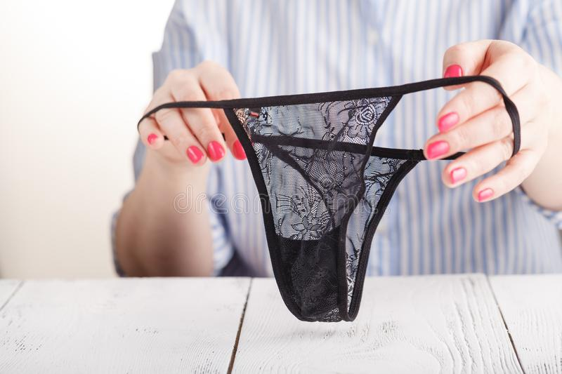 Female fingers hold lace panty stock photo