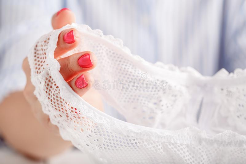 Female fingers hold lace panty stock photography