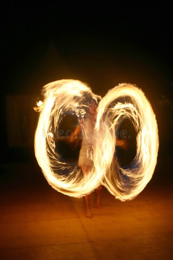 Female Fire juggler. Attractive Lady playing with the fire stock photo