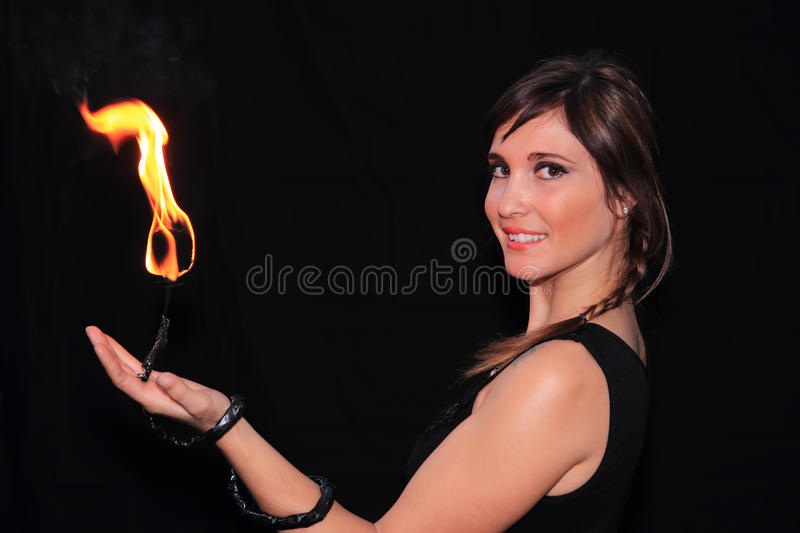 Female fire juggler. Fire juggler woman with flame over dark background stock images
