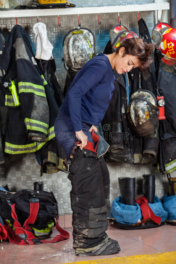 Female Firefighter Wearing Uniform At Fire Station. Full length of female firefighter wearing uniform at fire station royalty free stock photo