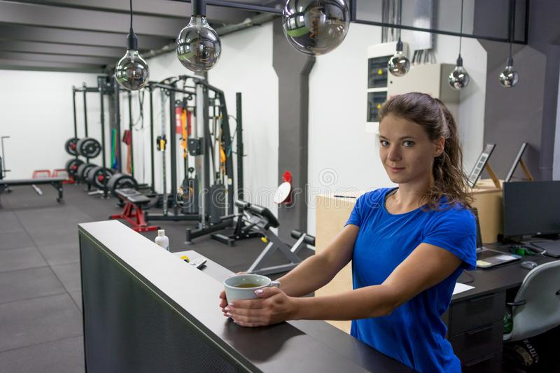 Female fitness assistant greeting you at homely gym bar with a cup of organic tea. stock photography