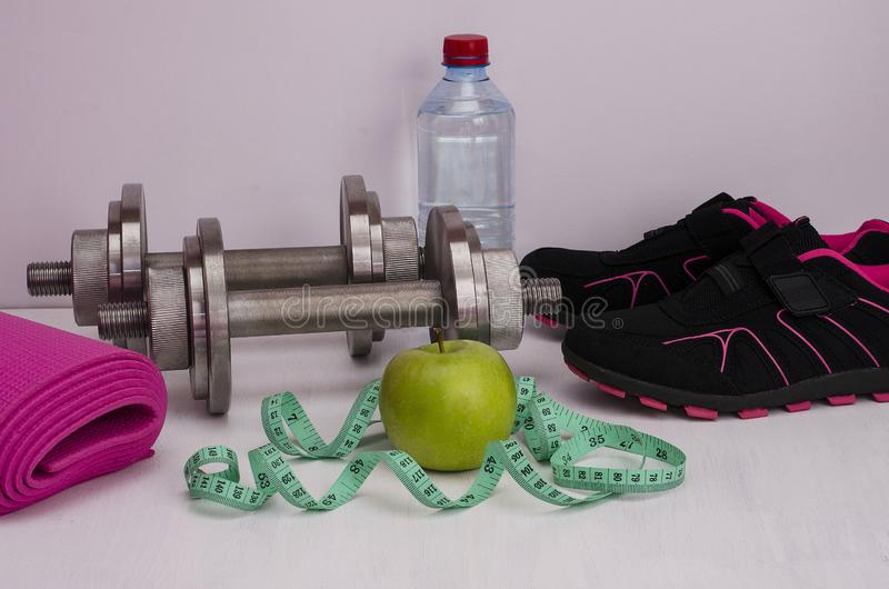Female fitness. Green apple with dumbbells, a bottle of water, a rug, running shoes and a tape royalty free stock photography