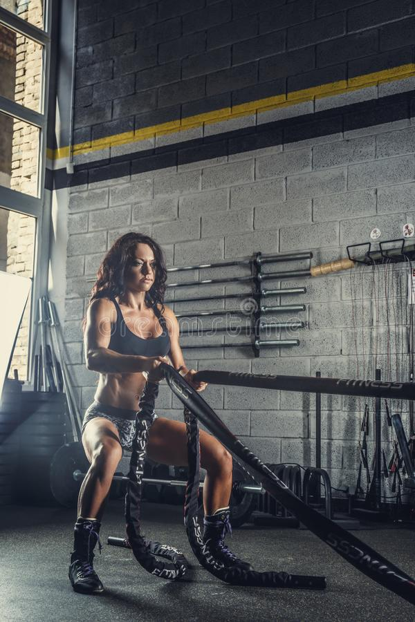 Female fitness model exercising with battle rope. stock photos