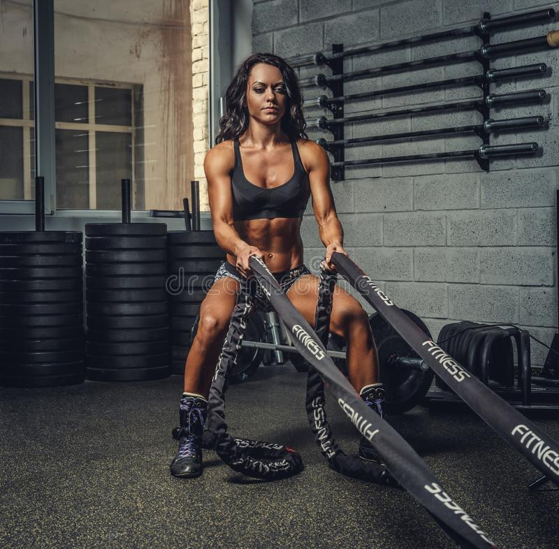 Female fitness model exercising with battle rope. royalty free stock photography
