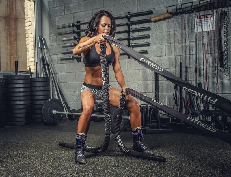 Female fitness model exercising with battle rope. stock images