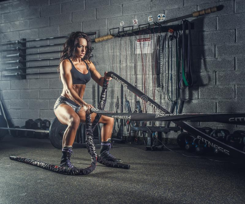 Female fitness model exercising with battle rope. royalty free stock photos