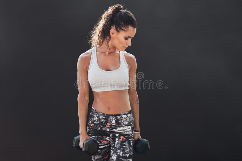 Female fitness model exercising with dumbbell. Young woman lifting weights for body building training over black background. Muscular weightlifting woman royalty free stock photos
