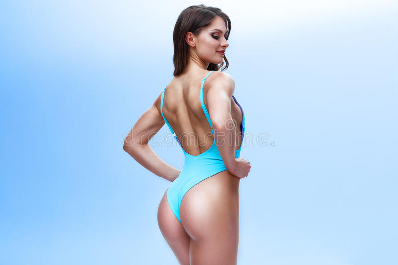 Female fitness model with a sporty body and long hair is posing in a light studio. Photo is made in a colourful and royalty free stock photos