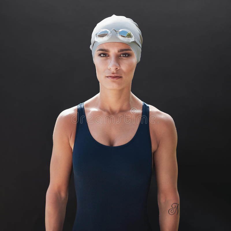 Female fitness model in swimsuit. Portrait of young woman in swimwear standing on black background. Female model in swimsuit royalty free stock photo
