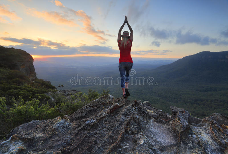 Female fitness stretch to the sky mountain top valley scene royalty free stock image