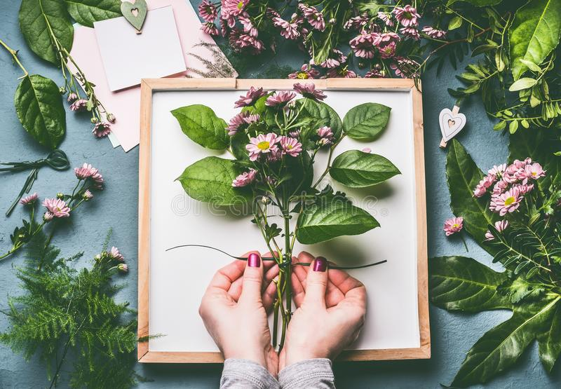 Female florist hands tied up with rope flowers bunch with green leaves on work space with white tray and blank card stock photography