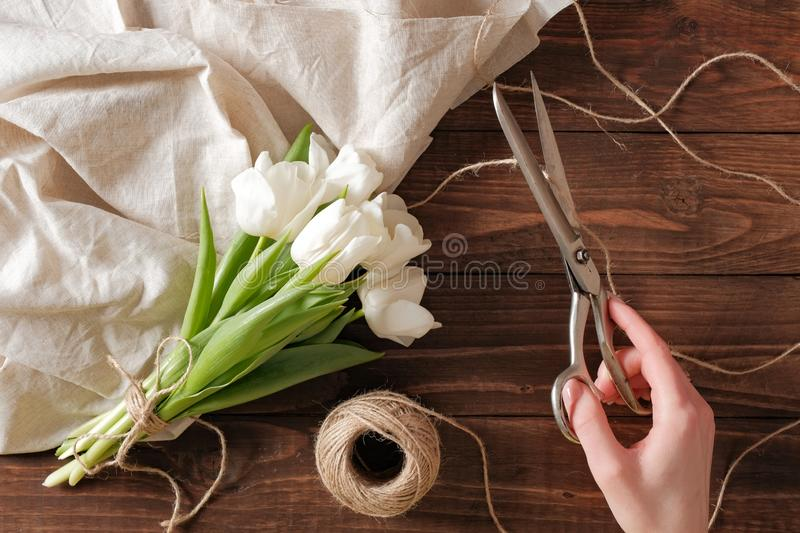 Female florist making beautiful bouquet of tulips for a spring holiday at flower shop stock photography