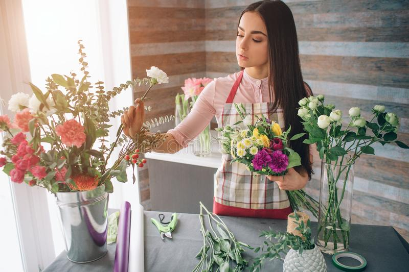 Female florist at work: pretty young dark-haired woman making fashion modern bouquet of different flowers. Women working royalty free stock photo