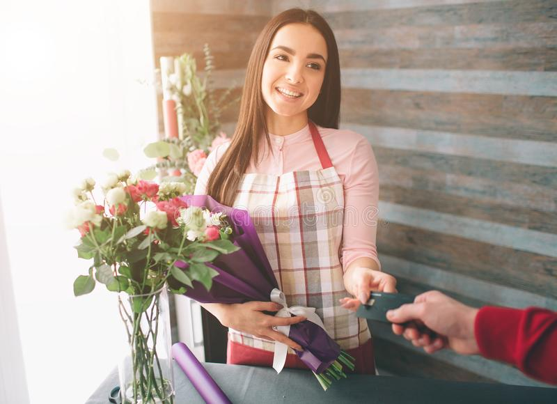 Female florist at work: pretty young dark-haired woman making fashion modern bouquet of different flowers. Women working royalty free stock photography