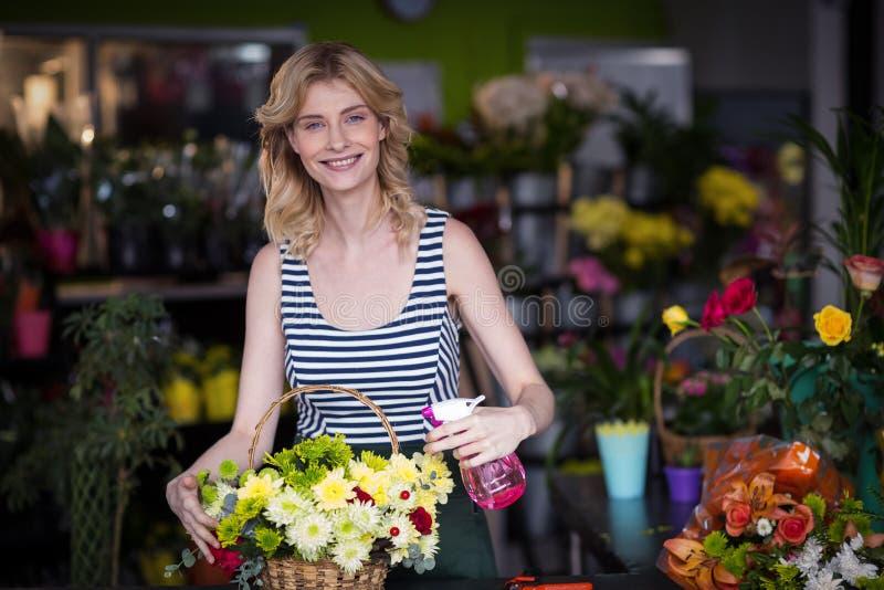 Female florists spraying water on flowers in flower shop. Portrait of smiling female florist spraying water on flowers in flower shop stock photos