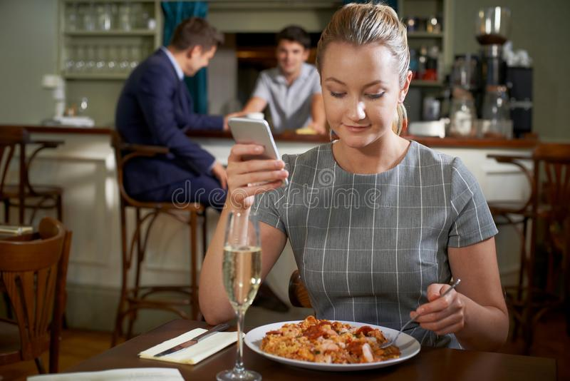 Female Food Blogger Posting Online Review Of Restaurant Meal Using Mobile Phone. Female Food Blogger Posts Online Review Of Restaurant Meal Using Mobile Phone stock photography