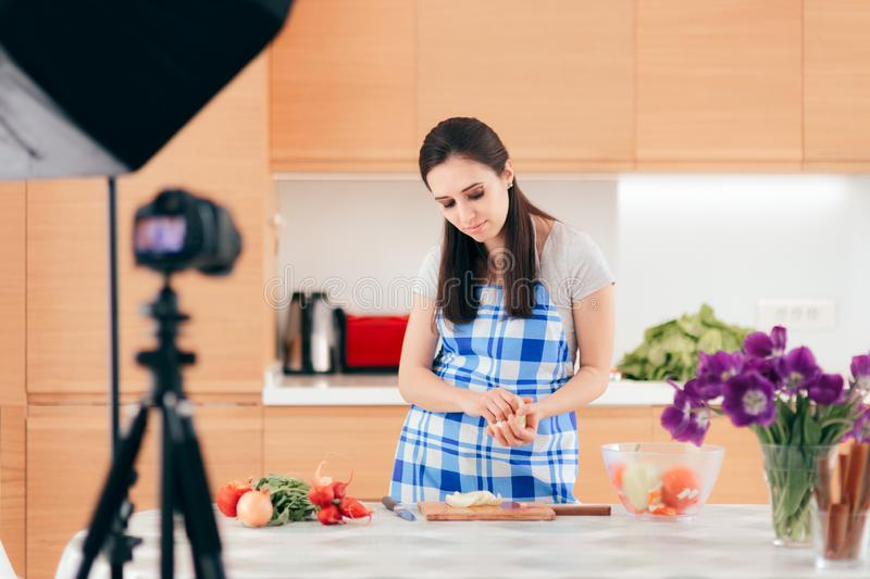 Female Food Vlogger Filming a Cooking Video in her Kitchen royalty free stock photo