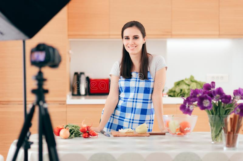 Female Food Vlogger Filming a Cooking Video in her Kitchen stock images