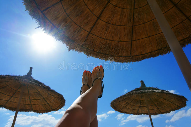 Female foot in flip flops on the beach. Beautiful female foot in flip flops on the beach royalty free stock photos