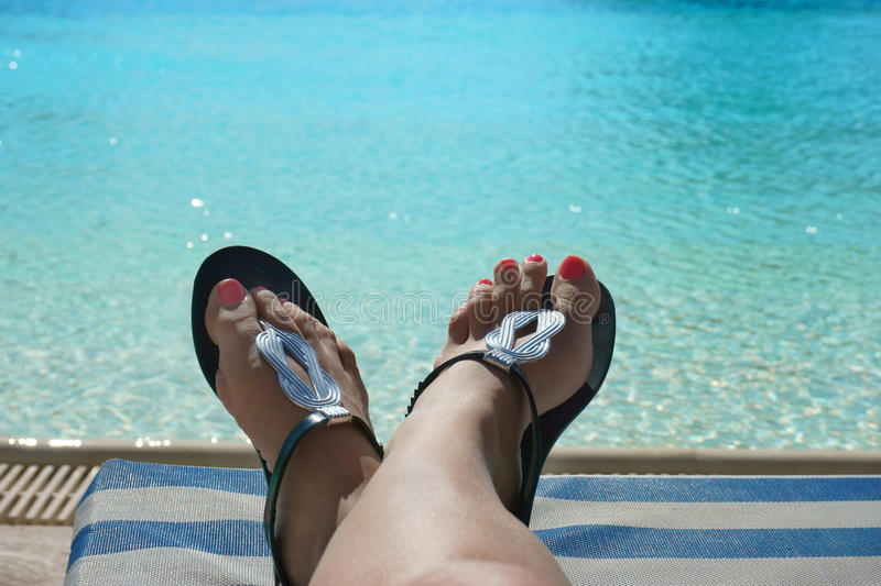 Female foot in flip flops on the beach. Beautiful female foot in flip flops on the beach royalty free stock photography