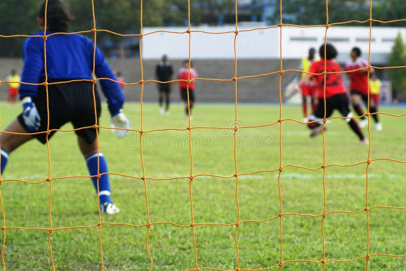 Female football match. A football or soccer match between female rival teams on a soccer field. Shot from behind the goalkeeper position with her ready to defend stock images