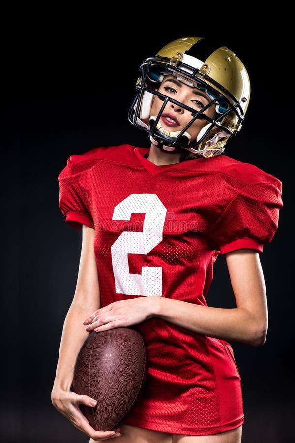 Beautiful female american football player in sportswear and helmet posing stock photo