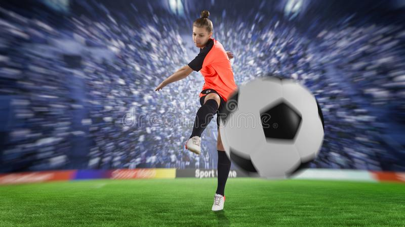 Female football player in orange uniform kicking the ball stock image