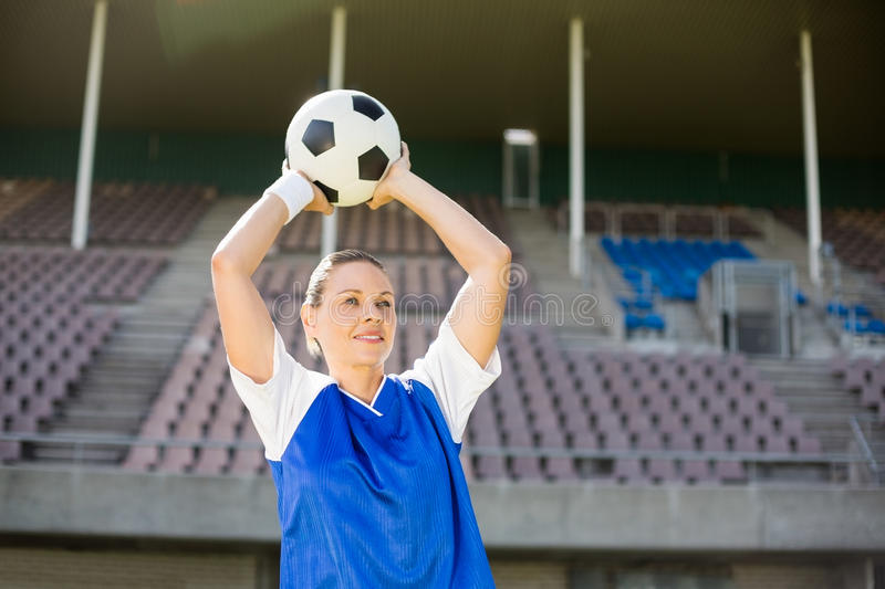 Female football player about to throw a football. In stadium stock photography