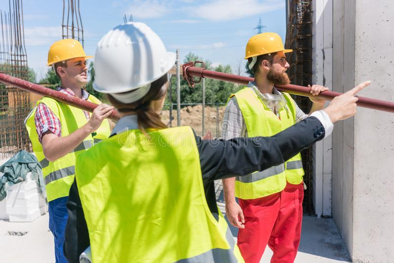Female foreman coordinating and guiding workers on the construction site royalty free stock image