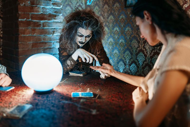 Foreteller guessing by hand over a crystal ball. Female foreteller guessing by hand over a crystal ball, witchcraft. Scary witch reads a magic spell, young women royalty free stock photos