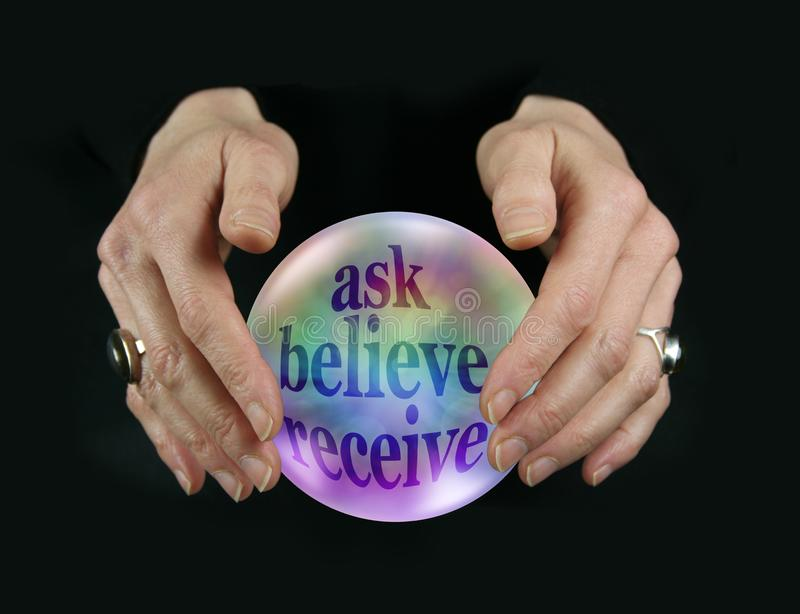 Crystal Ball Encouraging Ask Believe Receive. Female fortune tellers hands hovering around a crystal ball containing rainbow colored words ASK BELIEVE RECEIVE on royalty free stock photos