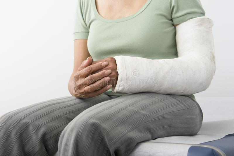 Female With Fractured Hand Sitting On Bed. Midsection of a female with fractured hand sitting on bed at clinic royalty free stock images