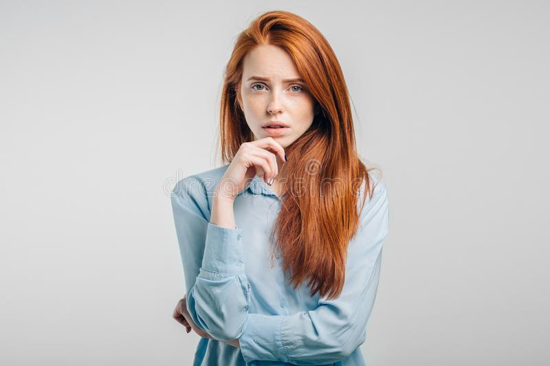 Female with freckles and pursed lips having disappointed unhappy look. At camera royalty free stock photos