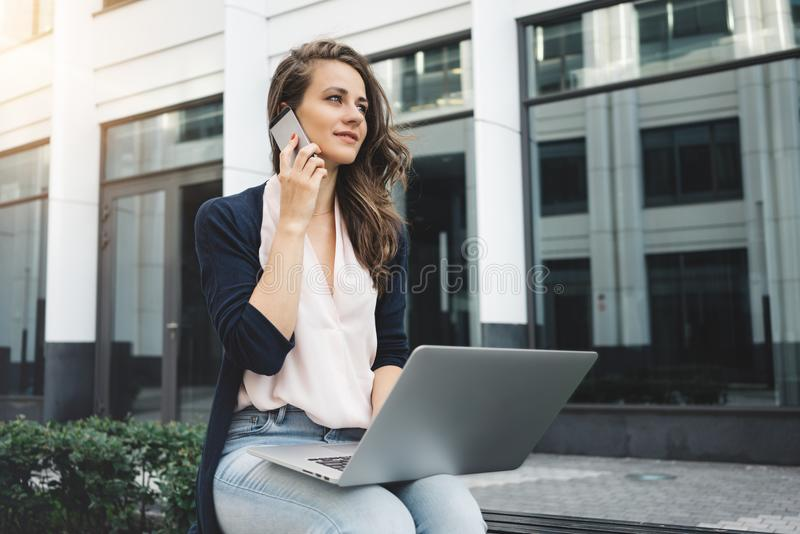 Female freelance working with laptop on street in business district and talking to customer by phone. Female freelance working with laptop on street in business stock photography