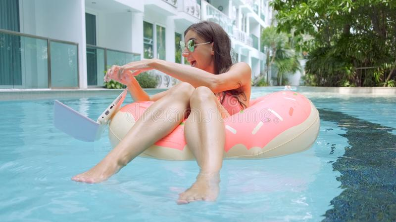 Female freelancer sits in an inflatable circle in the pool and drops the laptop into the water. Busy during the holidays royalty free stock image