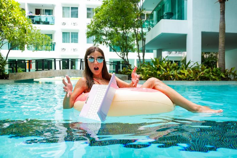 Female freelancer sits in an inflatable circle in the pool and drops the laptop into the water. Busy during the holidays stock images