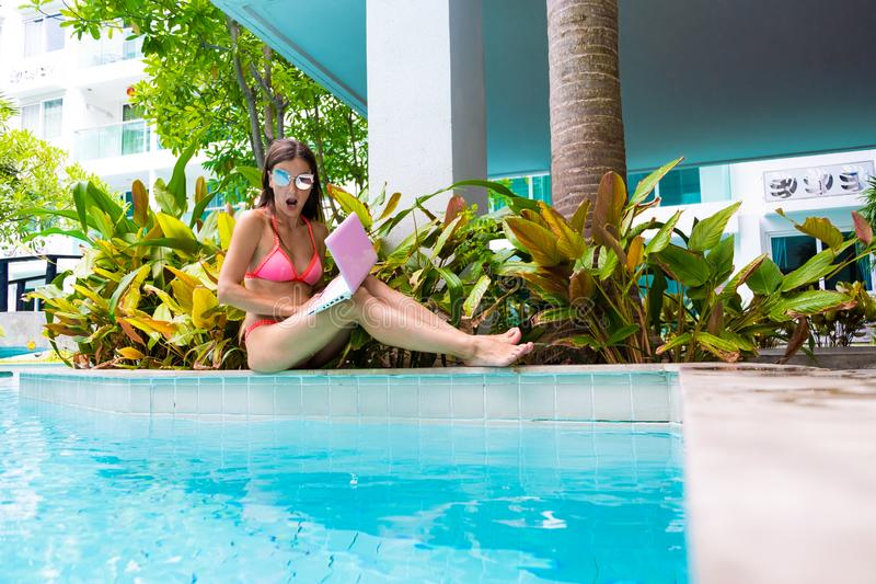 Female freelancer sits by the pool and throws the laptop into the water. girl is outraged, surprised, scared. selective stock photos