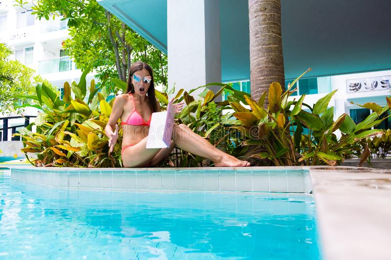 Female freelancer sits by the pool and works on a minicomputer, the girl drops her laptop into the water. Busy during stock photos