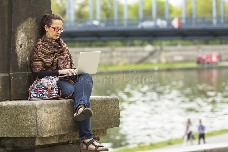 Female freelancer sitting outdoors with the laptop. Entrepreneur working with a laptop stock image
