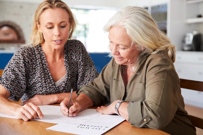 Female Friend Helping Senior Woman To Complete Last Will And Testament At Home stock images