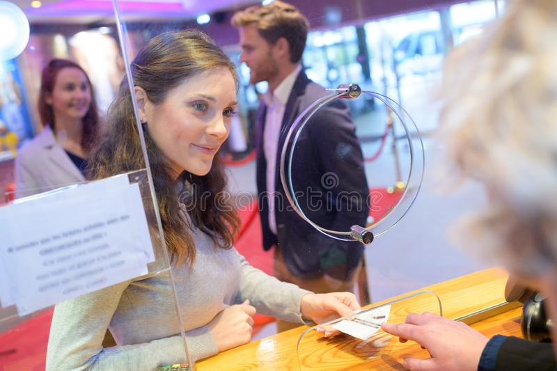 Female friends buying movie tickets royalty free stock photos