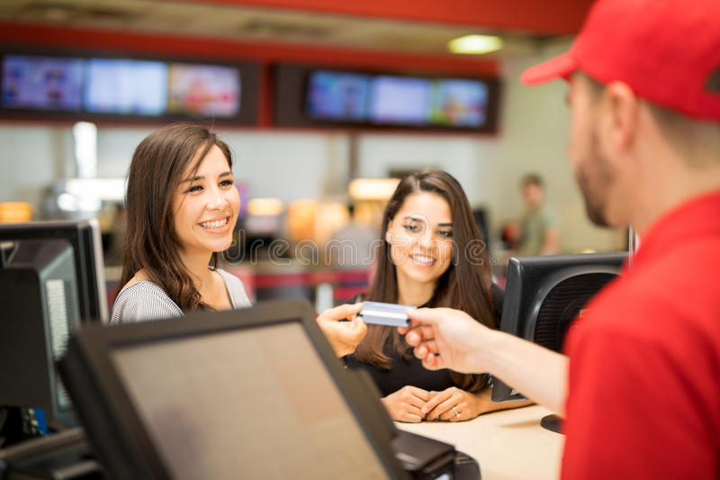 Female friends buying movie tickets. Point of view of a male worker getting a credit card from a pair of friends at the movie theater royalty free stock photo
