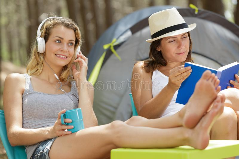Female friends doing their recreational activity outside tent royalty free stock images