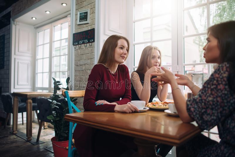 Female friends drinking coffee having a pleasant conversation in a cozy romantic restaurant.  royalty free stock image
