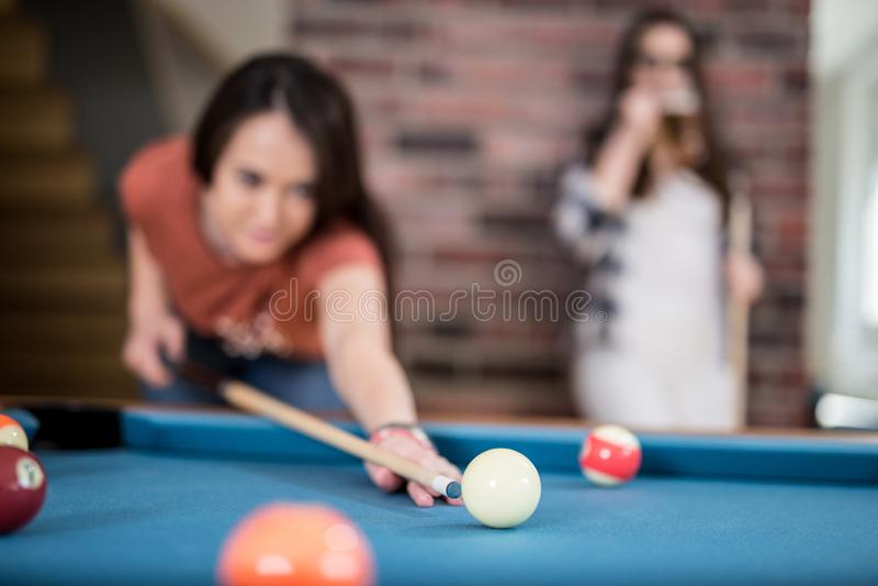 Female friends enjoying snooker game royalty free stock image